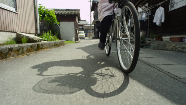 woman cycles along street, japan. - cycling stock videos & royalty-free footage