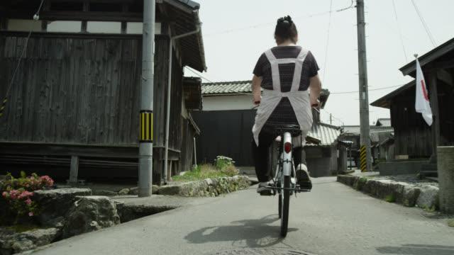 vídeos de stock e filmes b-roll de woman cycles past waterwheel, japan. - vedação