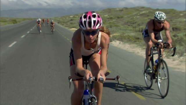 stockvideo's en b-roll-footage met ts ms woman cycling ahead of group of triathletes during race / strandfontein, western cape province, south africa - vrouwelijk