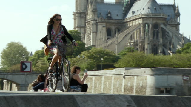 ws pan woman cycling along river, stopping to look at guidebook, notre dame in background, port de la tournelle, paris, france - promenade stock videos & royalty-free footage