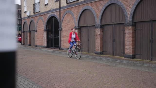vídeos de stock e filmes b-roll de woman cycling around town in her gym gear - estação do ano