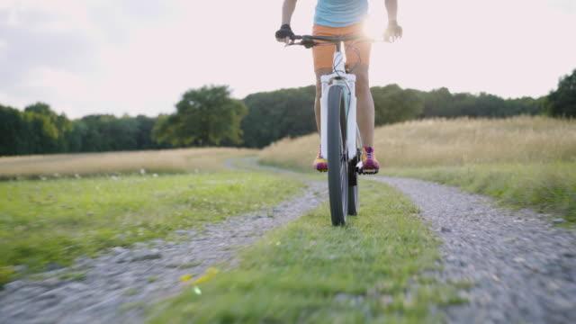 4K woman cycling down on electric mountain bike in rural landscape