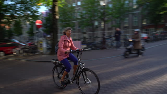 stockvideo's en b-roll-footage met woman cycling down street - stromend water