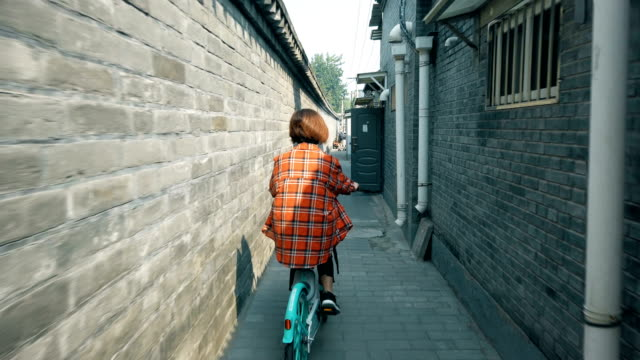 woman cycling in hutong(lane),beijing,china. - plaid shirt stock videos & royalty-free footage
