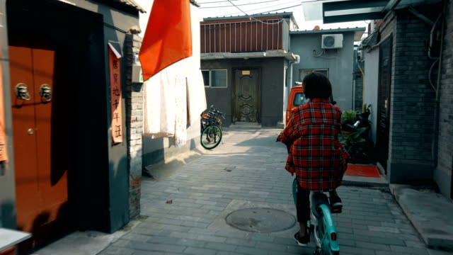 woman cycling in hutong(lane),beijing,china. - top capo di vestiario video stock e b–roll