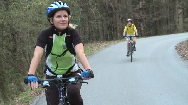 slo mo ms ds woman cycling in rural landscape, man in background, vrhnika, slovenia - vrhnika stock videos & royalty-free footage