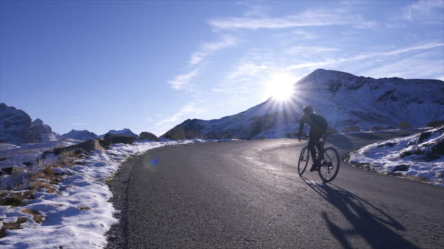 woman cycling on bicycles, riding on road bikes in the winter. - uphill stock videos & royalty-free footage