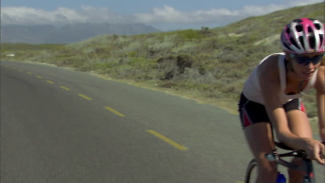 TS WS Woman cycling on remote road during race / Strandfontein, Western Cape Province, South Africa