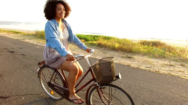 Woman cycling on sunny road