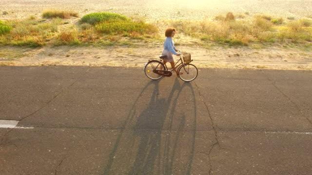 kvinna som cykling på soliga road - sanddyn bildbanksvideor och videomaterial från bakom kulisserna