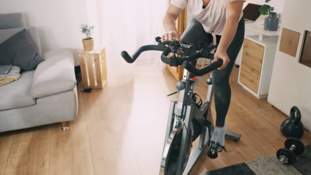 slo mo woman cycling on the exercise bike at home - exercise bike stock videos & royalty-free footage
