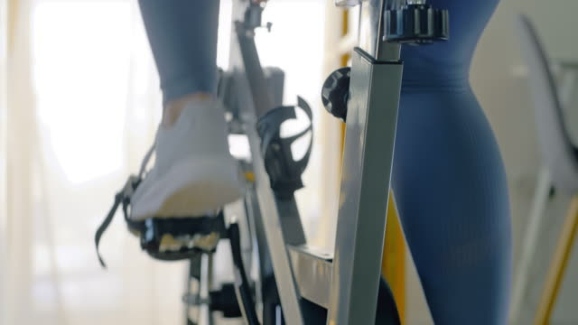 slo mo woman cycling on the exercise bike at home - focus on foreground stock videos & royalty-free footage