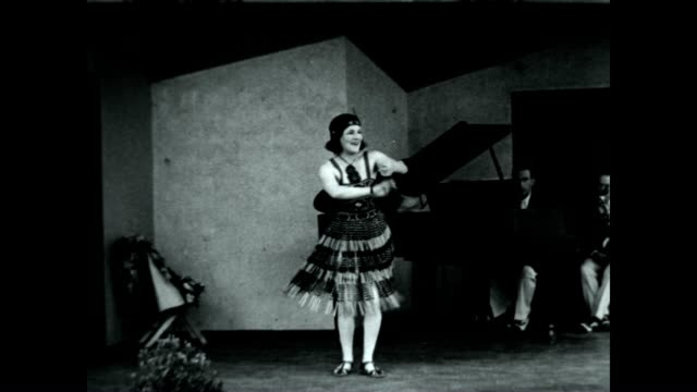 A woman dances and performs to Piano accompaniment while tossing Argentinian bolas