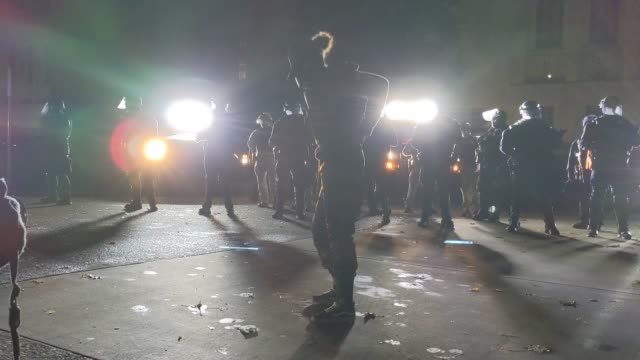 """woman dances as oregon state police and salem police guard the area during dueling black lives matter and """"stop the steal"""" protests on november 7,... - salem oregon stock videos & royalty-free footage"""