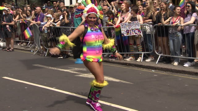 A woman dances during the colourful Pride march in central London
