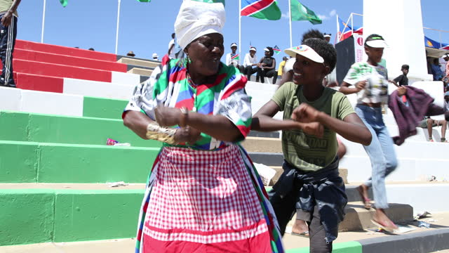 a woman dances with a preadolescent while people play music during the celebration of the 29th anniversary of liberation of namibia at the... - pre adolescent child stock videos & royalty-free footage