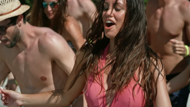 slo mo woman dancing a group dance with her friends outside in her bathing suit - swimwear stock videos and b-roll footage
