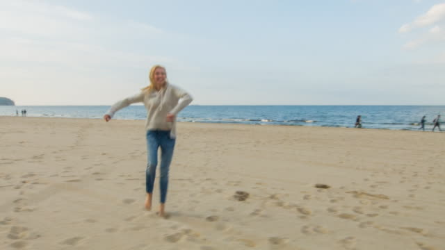 woman dancing and jumping on the beach - older woman fun stock-videos und b-roll-filmmaterial