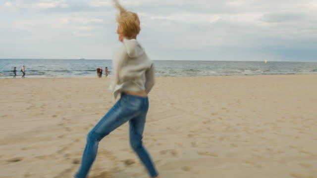 woman dancing and jumping on the beach - weitwinkelaufnahme stock-videos und b-roll-filmmaterial