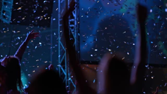 SLO MO Woman dancing at concert in confetti rain