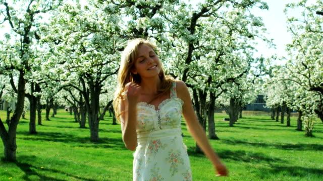 vídeos de stock e filmes b-roll de woman dancing in a grove of flowering trees - só uma menina adolescente