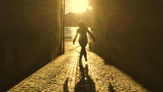 woman dancing in a narrow street with sunbeam and shadow - wand stock-videos und b-roll-filmmaterial