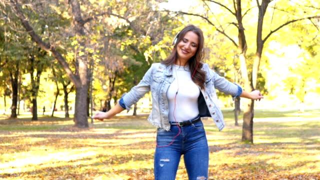 vídeos de stock, filmes e b-roll de dança da mulher nas folhas do outono - parque natural