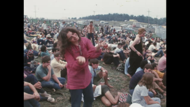woman dancing in the crowd at the woodstock music festival at max yasgur's dairy farm in bethel, new york. - hippie stock videos & royalty-free footage
