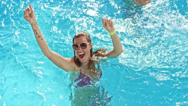 stockvideo's en b-roll-footage met slo mo vrouw dansen in het zwembad op een pool party met haar vrienden - poolparty