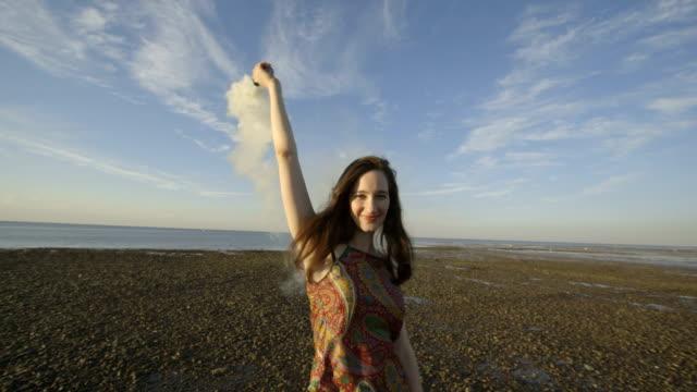 Woman dancing on beach with smoke bomb