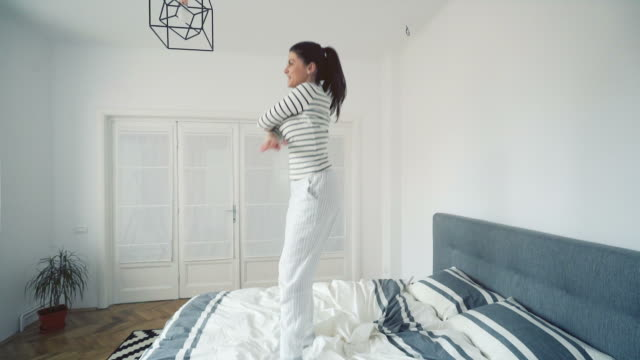 Woman dancing on bed.
