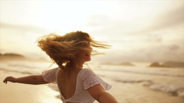 frau tanzt am meeresstrand bei sonnenuntergang - blondes haar stock-videos und b-roll-filmmaterial