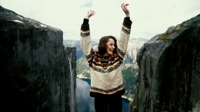 woman dancing on the background of  scenic view of lysefjorden from kjerag mountain - top garment stock videos & royalty-free footage