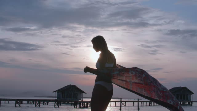 a woman dancing, traveling with a sarong on a deck over water at sunset. - sarong stock videos & royalty-free footage