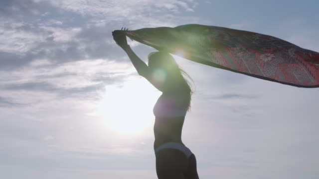 a woman dancing, traveling with a sarong on a deck over water at sunset. - sarong video stock e b–roll