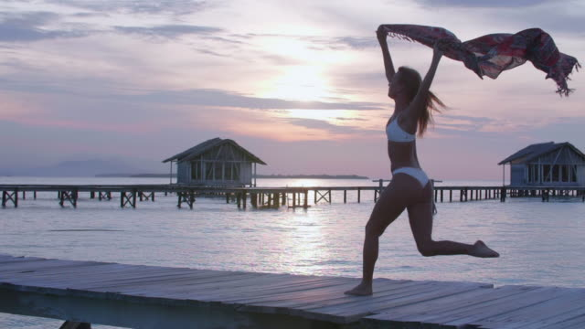 a woman dancing, traveling with a sarong on a deck over water at sunset. - sarong stock-videos und b-roll-filmmaterial
