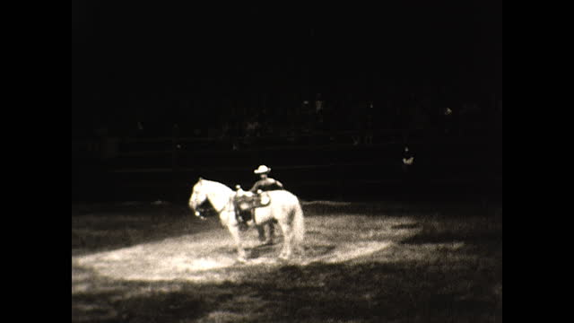 woman dancing under the spotlight with a baton; various views of cowboys attempting to tame horses in the rodeo; cowboy standing on horseback doing... - tame stock videos & royalty-free footage