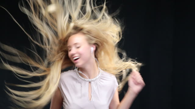 ms woman dancing wearing earphones, long blond hair moving in wind / london, greater london, united kingdom - dance studio video stock e b–roll