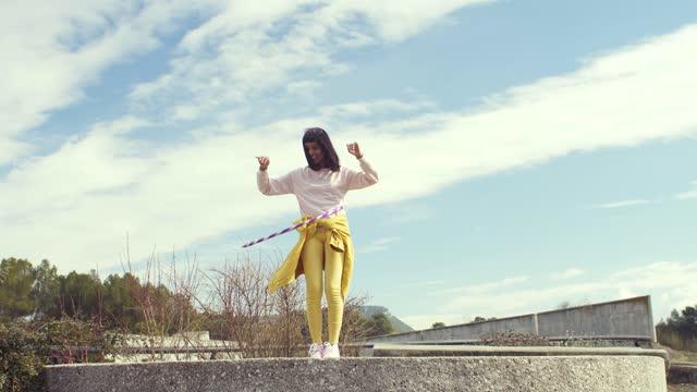 vídeos y material grabado en eventos de stock de woman dancing with a hula hoop - distante