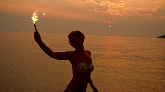 slo mo woman dancing with a sparkler on the beach - sunglasses stock videos & royalty-free footage