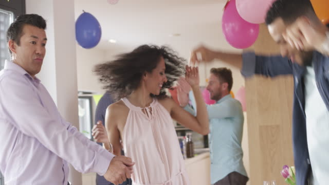 Woman dancing with two male friends at a birthday party