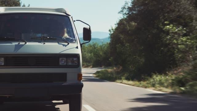 donna penzoloni gambe dalla finestra del furgone durante il viaggio - furgone video stock e b–roll