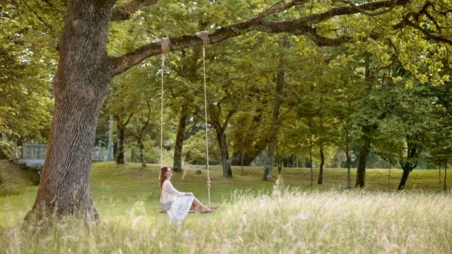 vídeos de stock e filmes b-roll de slo mo ds mulher daydreaming no balanço em natureza - equipamento de parque infantil