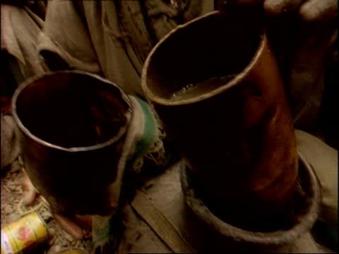 vidéos et rushes de mcu woman decanting brown water into drinking cup, ethiopia, africa - eau potable