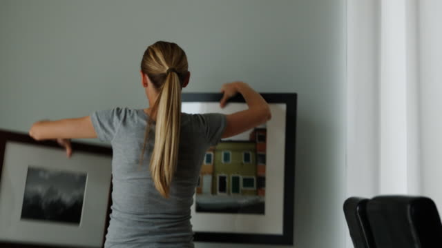 woman deciding which picture to hang on the wall - see other clips from this shoot 1418 stock videos & royalty-free footage