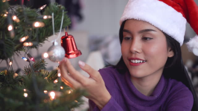 Woman decorates the Christmas tree.