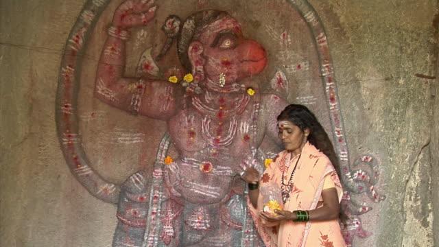 MS, Woman decorating carving of Hanumana with flowers, Hampi, Karnataka, India