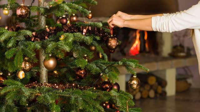 woman decorating christmas tree - albero di natale video stock e b–roll