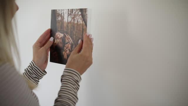 frau schmückt ihre wand mit foto - wand stock-videos und b-roll-filmmaterial
