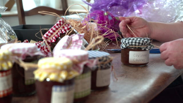 Woman decorating homemade Christmas gift preserves.